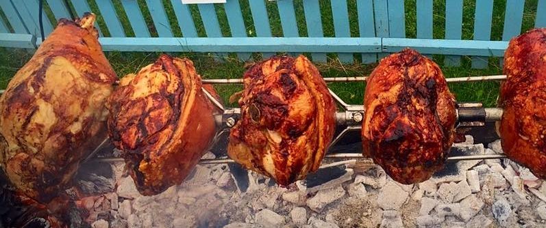 Dingley Dell pork legs cooking over charcoal.jpg
