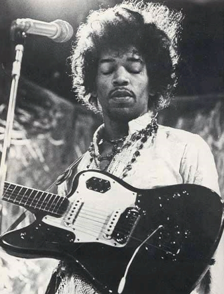 Jimi Hendrix on stage with a custom color Jaguar in 1968