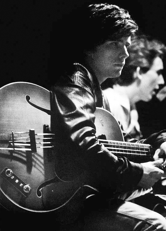 Stuart Sutcliffe on stage with George Harrison.