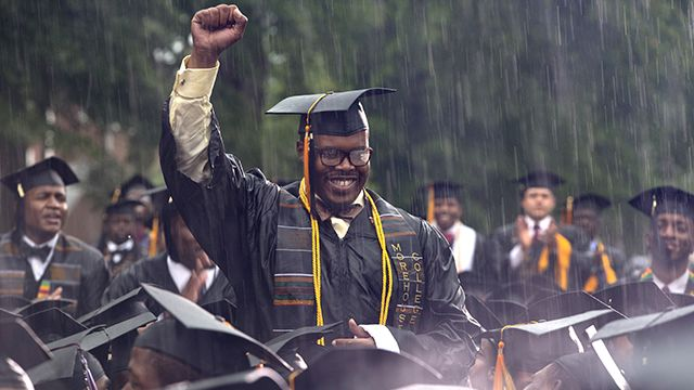 GRADUATE FREDERICK ANDERSON STANDS IN THE POURING RAIN AS PRESIDENT BARACK OBAMA ACKNOWLEDGES HIM DURING THE MOREHOUSE COLLEGE 129TH COMMENCEMENT CEREMONY ON SUNDAY, MAY 19, 2013, IN ATLANTA. (AP PHOTO/CAROLYN KASTER)
