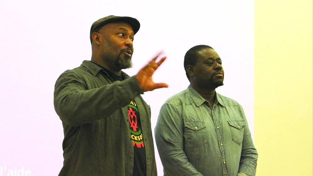 Kali Akuno (left) with Eros Sana, a leading organizer for racial justice, in Paris, France, addressing a gathering during the UN climate change negotiations.