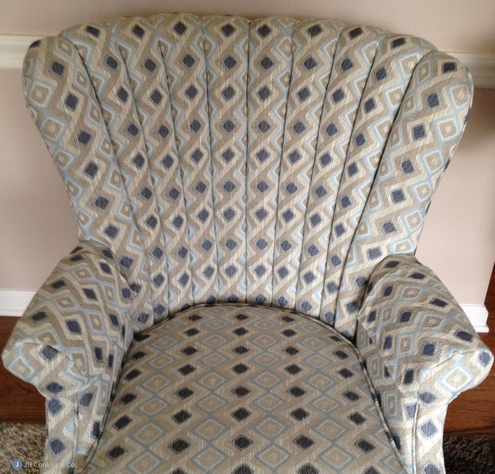 Channel-back arm chair in a tough vertical pattern.