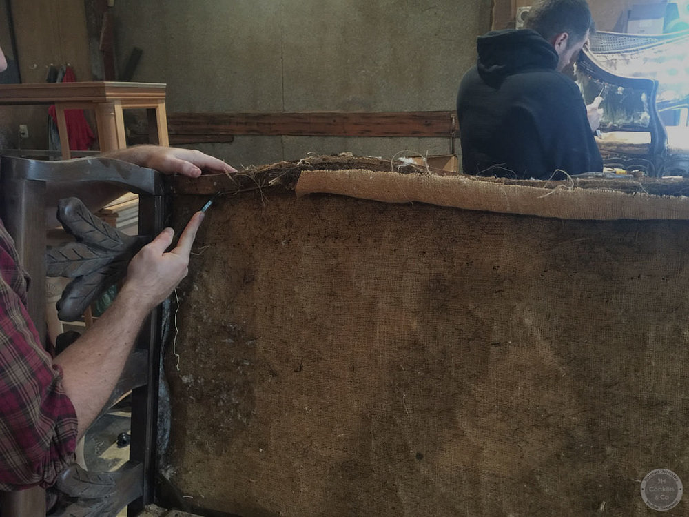 Removing the upholstery from a sofa and chairs.