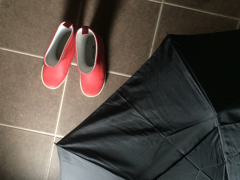 Rain boots and umbrella on the tile floor