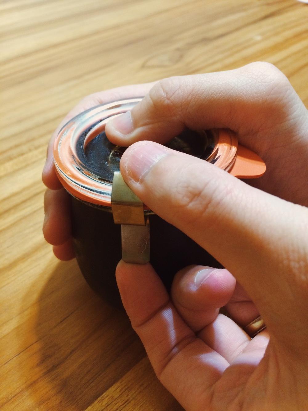左手壓住瓶蓋、右手由下往上掰開扣環。