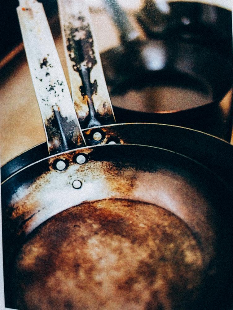這是日本某蛋包飯店家已經連續使用至少五六年以上,每天使用的同樣材質鐵鍋,可以看到表層的皮膜都已經掉落然後又重新燒成金黃色的表面,就連把手處也已經掉落,但完全不影響使用,只有更好用。