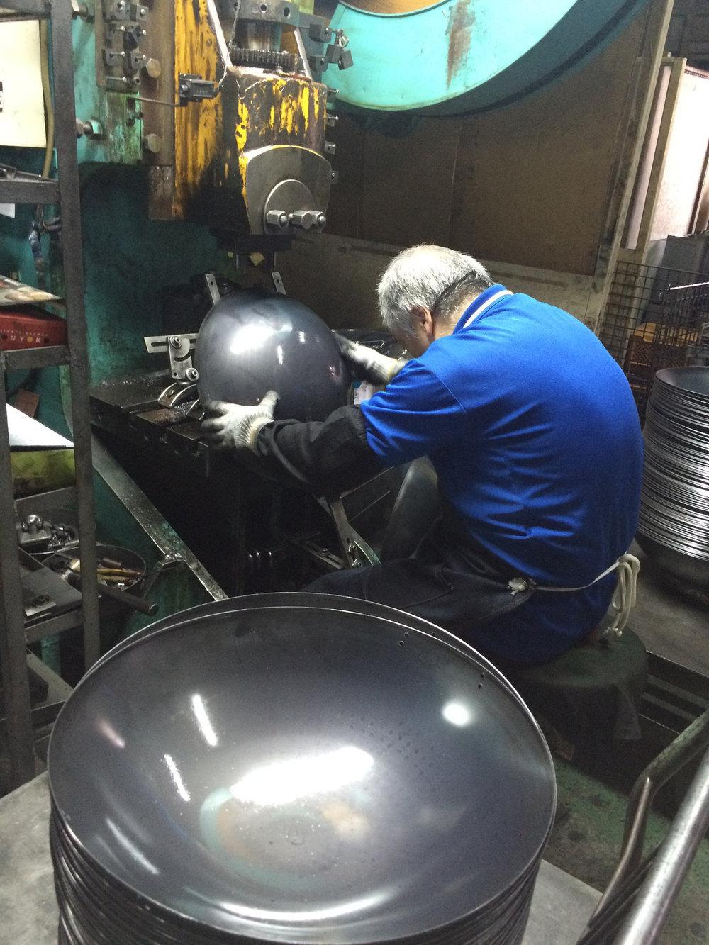 02|成形 - 機器從上往下沖壓成圓形之後,就交由經驗老到的師傅手工修邊成形、鑽手把孔。