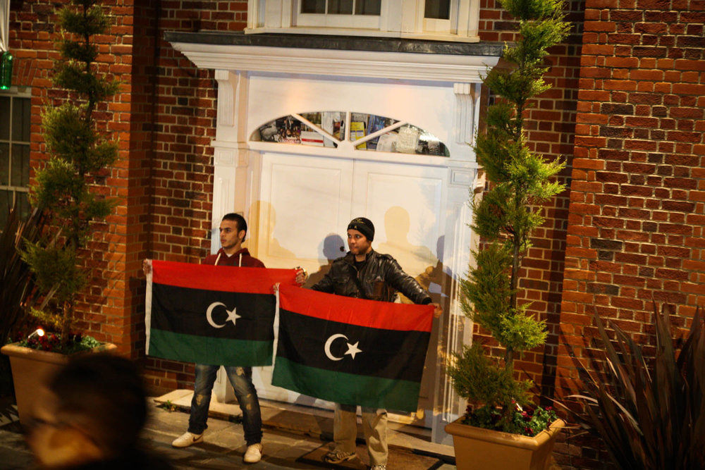 Libya protesters in front of Saif Gaddafi's multi-million pound mansion in Hampstead, London. Purchased with the stolen money from the Libyan people, Gaddafi and his progeny were living in the lap of luxury, whilst the people suffered. The house was occupied by non-Libyan squatters who would not let us in. One of us forced their way through the back door and opened the door for us.