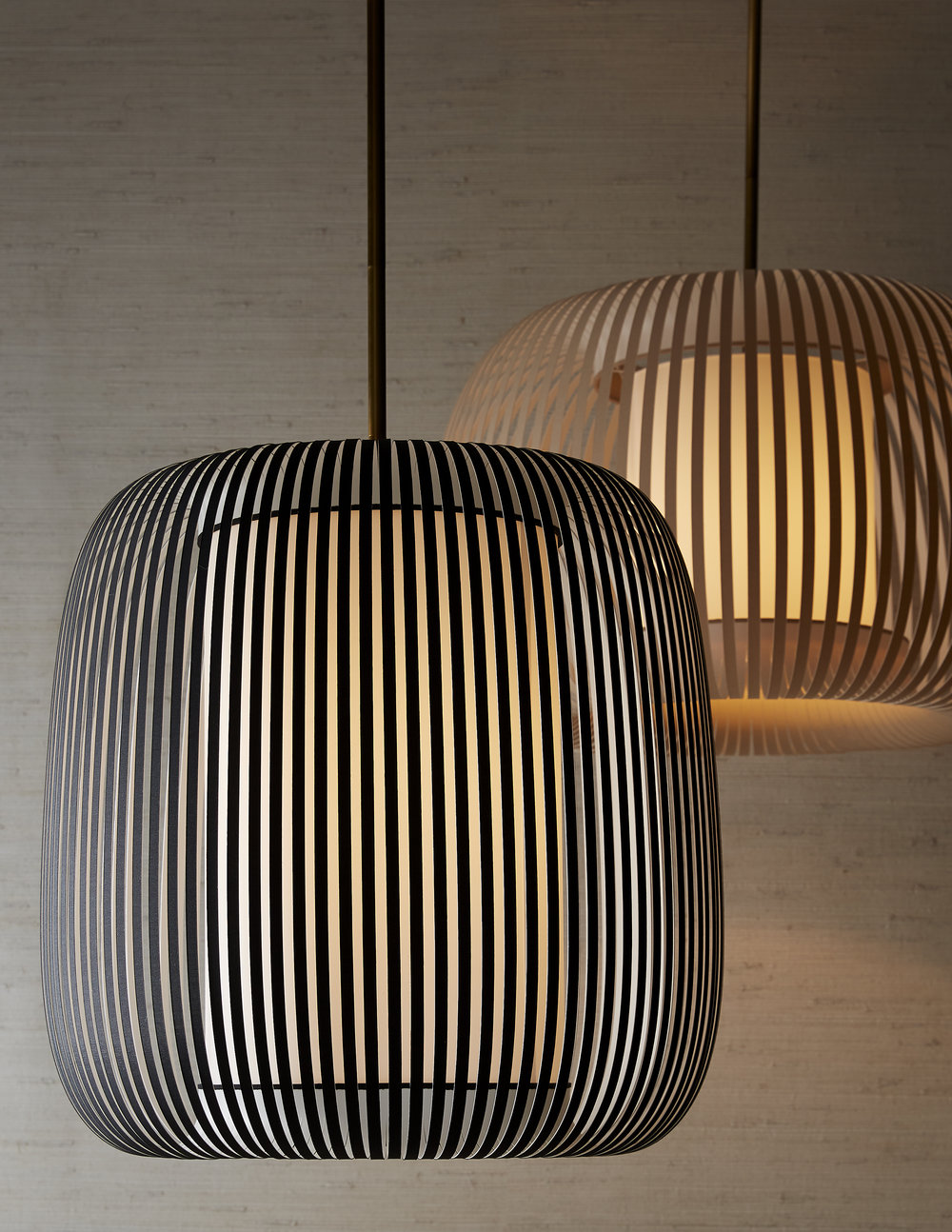 Mia Pendant - Like a magnetic field surrounding the central lantern, almost 100 strips of upholstered banding are made to create each of these pendants. These pendants manage to be both sturdy and lend an open, airy feel to any space they're installed.