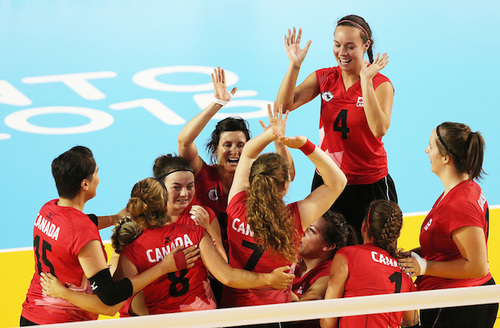 2015 Canadian women's sitting volleyball team celebrate as a team on the court