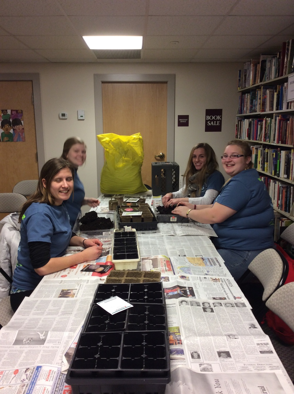 Four of the fourteen students who helped shovel ice from the parking lot, tutored in the use of electronic devises and digital media, shelved books, and started seeds.