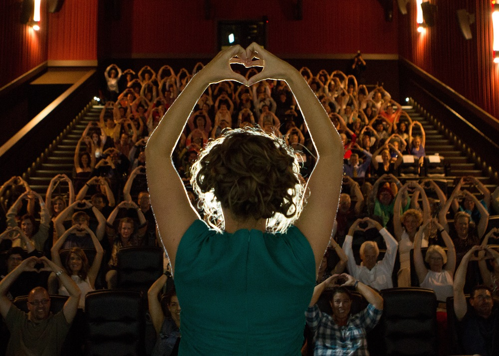"Download High Res Image of Dr. Rhea Zimmerman Komarek ""Love Bombing"" with the audience at the Love Bomb World Premier.  Photo Credit:  Briana Marie Photography.  For press use only in association with the film Love Bomb.  Any other use will be considered copyright infringement."