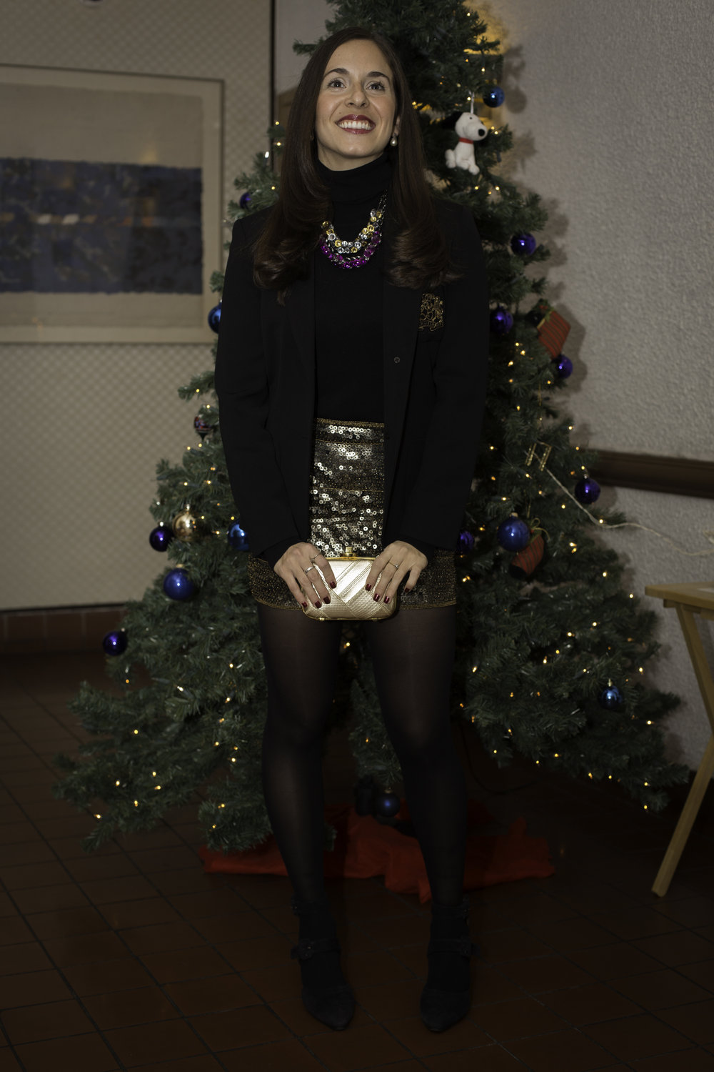 Standing by the tree at a holiday party wearing my Ralph Lauren black with gold crest blazer, a Zara black turtleneck, gold Topshop sequin mini skirt, black tights, and vintage black suede pumps. My gold clutch is a Coach python holiday clutch. Photography by Francisco Graciano.