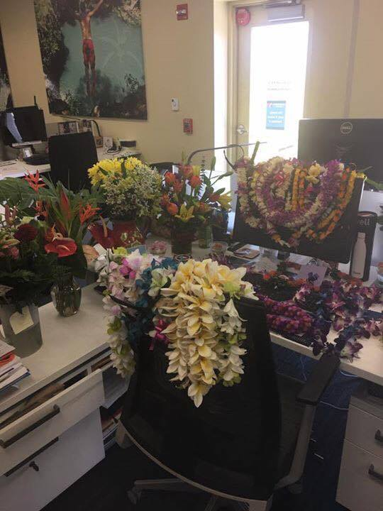 Lei covers Britt Reller's desk at the Hawaiian Airlines in-flight division. (Image: Facebook/Remembering Britt Reller)
