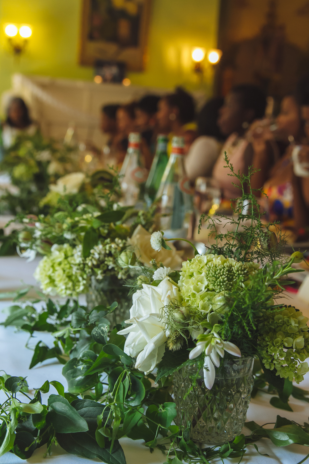 The client wanted a single long table for her tea party with lush white and green flowers to adorn the table.