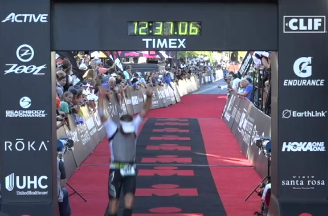 A Good Wolf athlete triumphantly crossing the finish at his first Ironman.