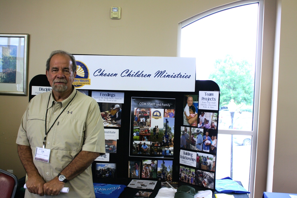 A missionary stands with his display in the cafeteria for NGU's Global Missions Week.