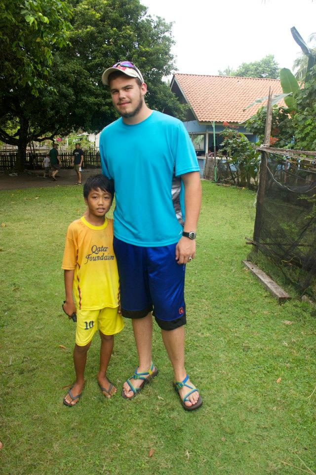 Nick takes a photo with a little boy he met during his time in Indonesia.
