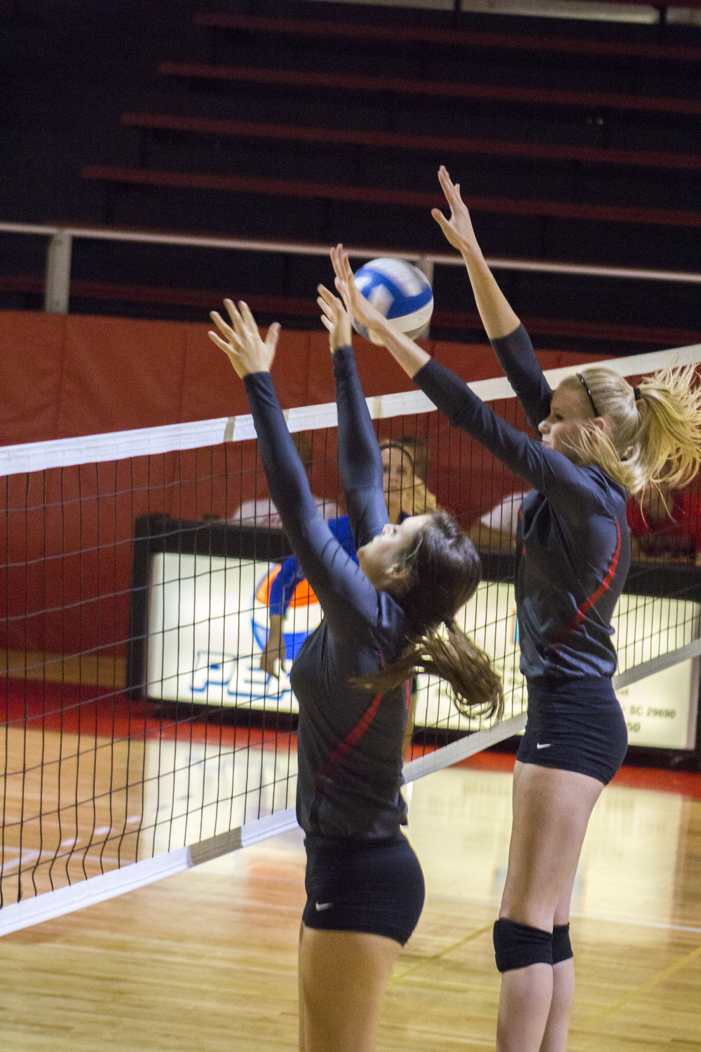 Freshman Kenzie Pierce and sophomore Rachel Burts jump up to tip the ball to the opponent's side.