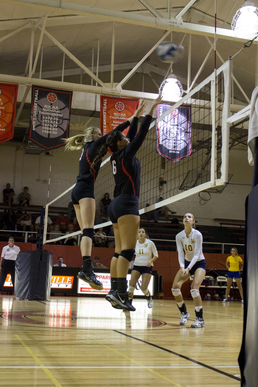 Senior Elizabeth James and sophomore Rachel Burts jump up to block a spike.