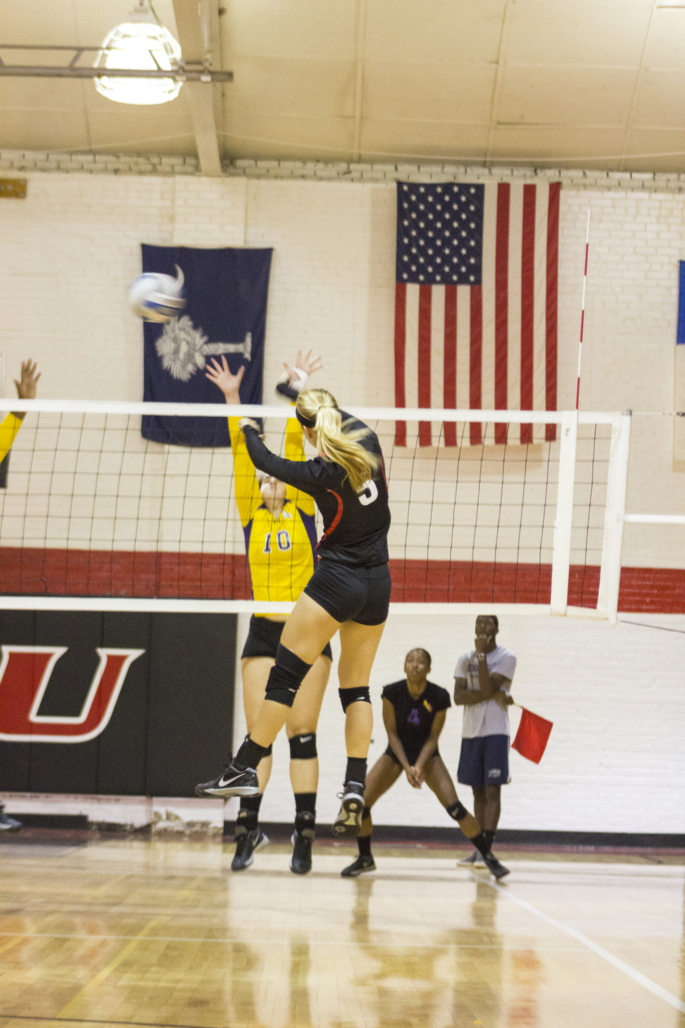 Junior Taylor Dupes jumps to spike the ball across the net between two opponents.