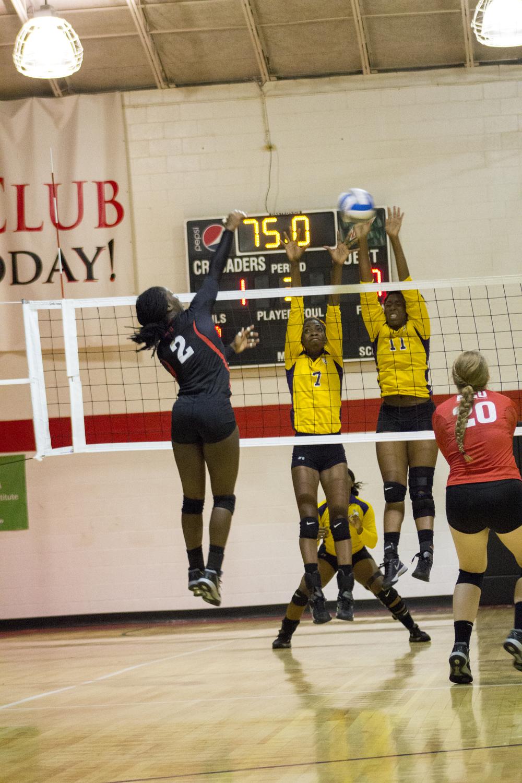 Junior Yomi Adeyeye spikes the ball at the opposing team.