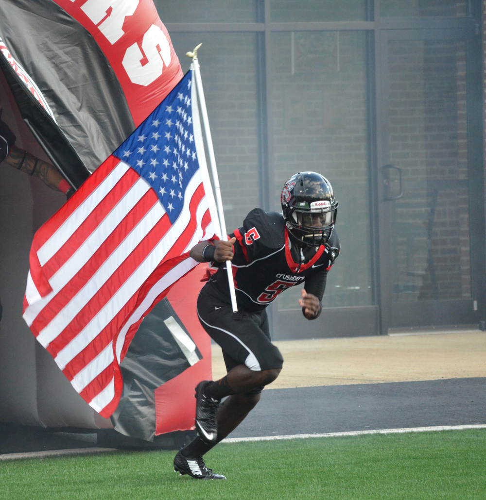 Player #5, Quantel Mack, starts off the game by charging out of the tunnel while carrying the American flag
