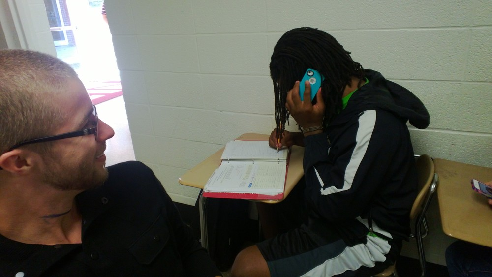 FreshmanEddie Studyvance (right) takes a phone call during class.
