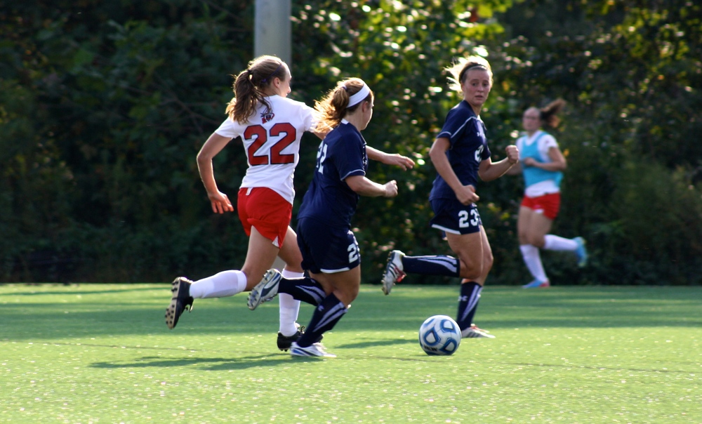 #22, Kathryn Allen, runs between two opponents in order to reach the ball.