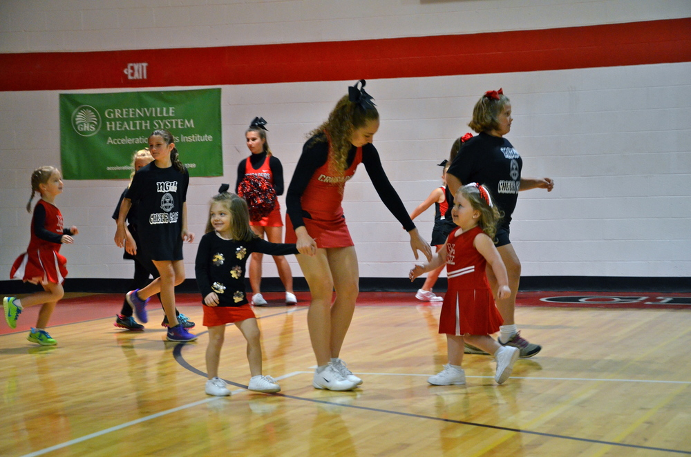 A cheerleader lends a helping hand to help the young cheerleader in the game.