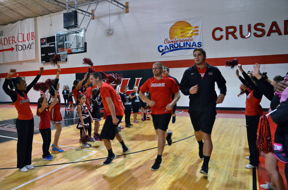 A tunnel of mini-Crusaders encourage the male cheerleaders as they run through.