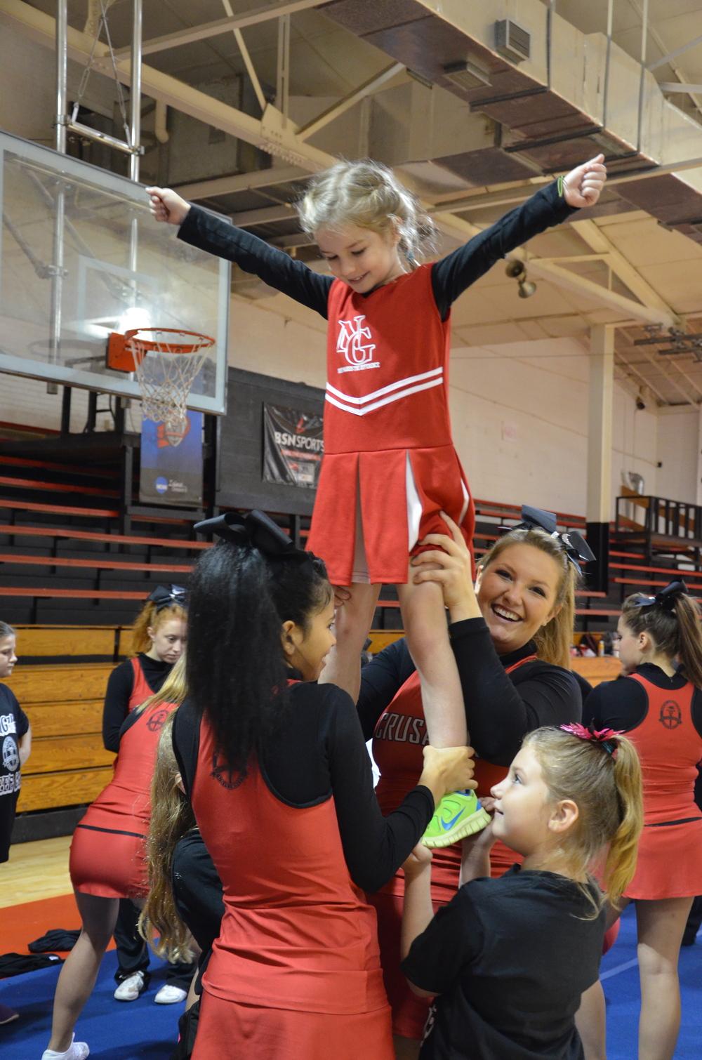 A little girl getting big help to be like the cheerleaders
