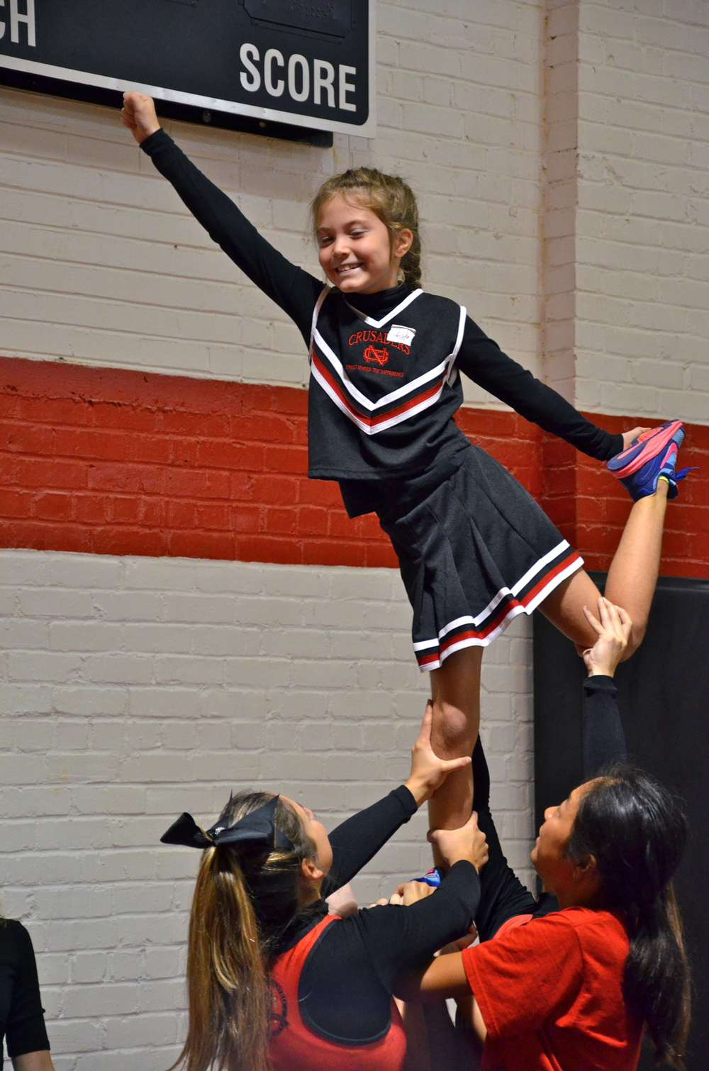 Smiles show all around for this cheery tyke as she holds her stance at NGU's cheer camp.