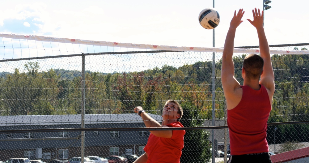 A student sends the ball over the net.