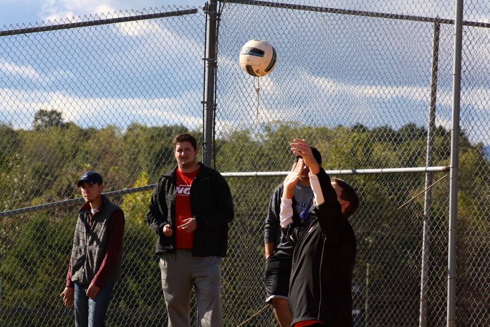 A student serves the ball by tossing it into the air.