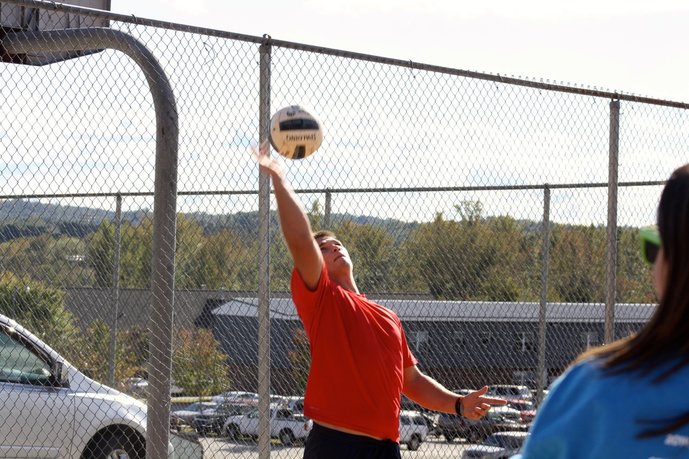 A students smacks the ball.