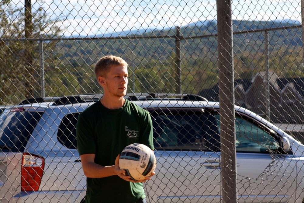 A student waits for his signal to serve the ball.