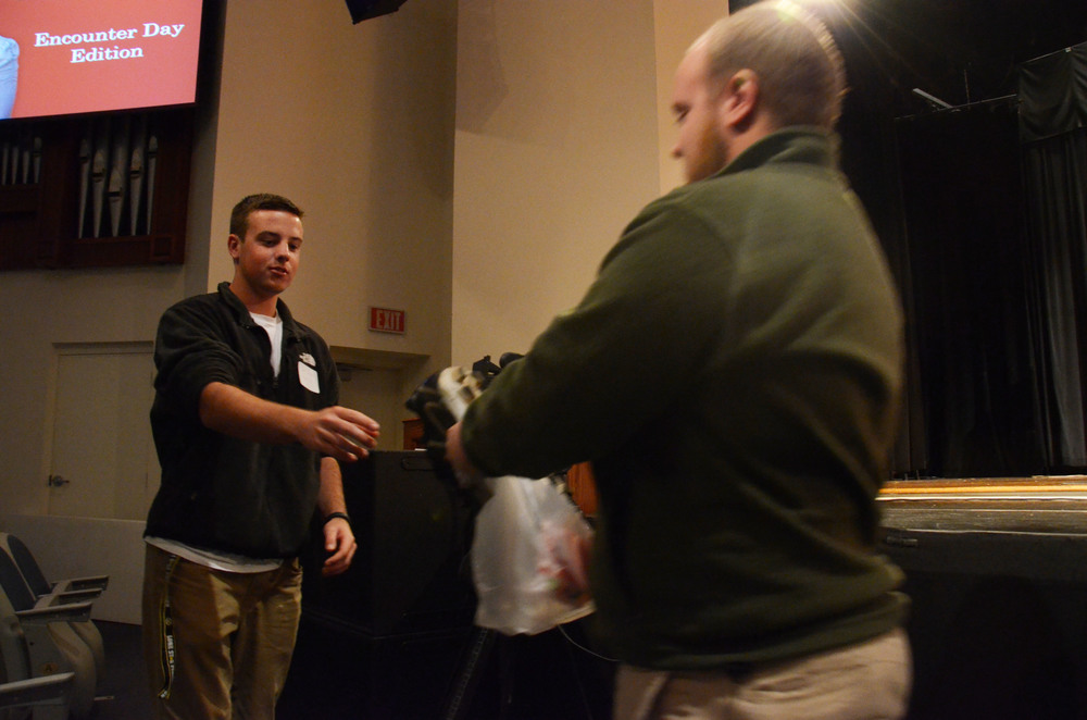 A potential student receives a prize delivered by Travis Brian, a Campus Ambassador.