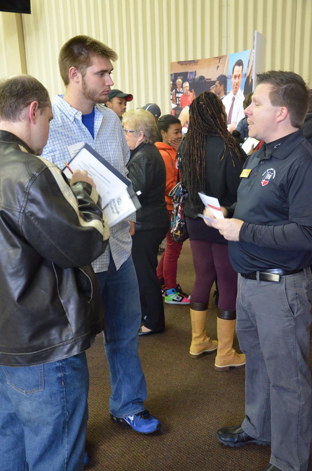 Christopher Davis, a fine arts teacher, talks to a potential student about the Fine Arts Department.
