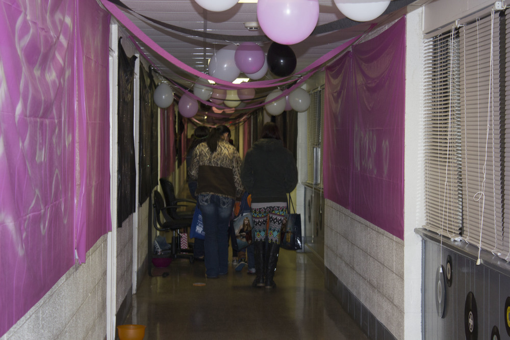 Some kids and their moms walk through bottom Simpson, decorated with a Grease theme.
