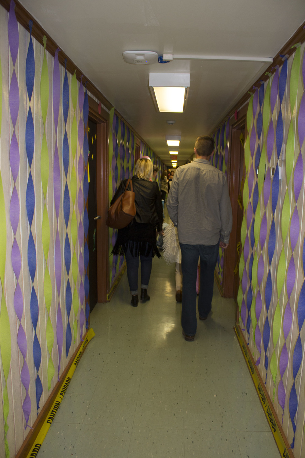 Parents walk down Emery's Monsters Inc themed dorm with their kids.