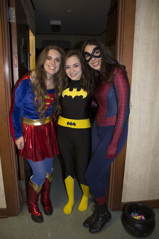 Sophomores Devon Parker and Celina Schwartz, along with Celina's sister Sophie, sport their festive Halloween superhero outfits.