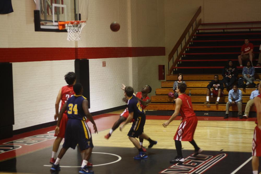 Three NGU JV basketball players attemptto get the rebound.