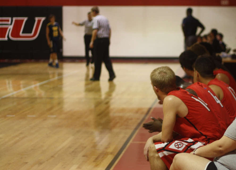 NGU team observes their teammates on the court.