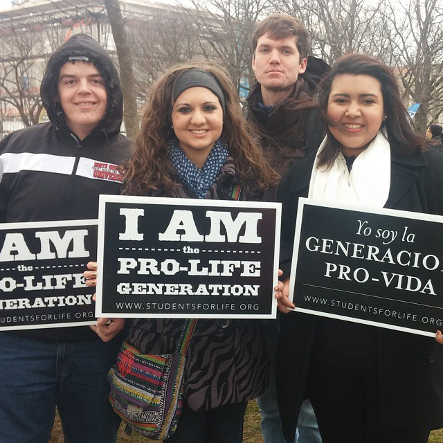 Aivarenga joins fellow NGU students in holding up her pro-life poster for the march against abortion.