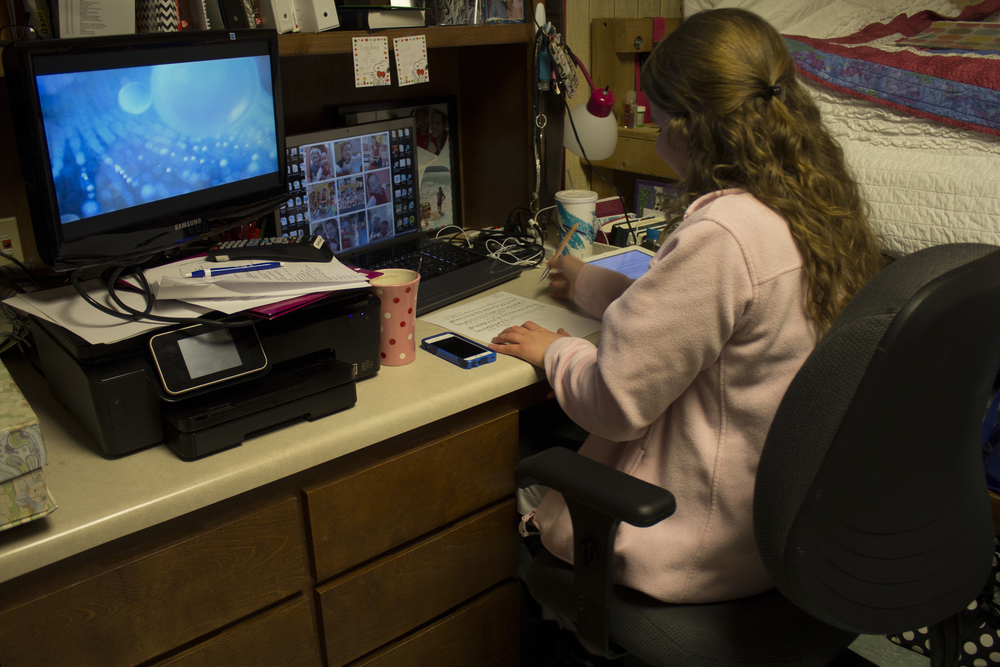 Sophomore Marianne Woodard enjoys the peace and solitude of her dorm room to work on some homework while a few of her friends pop into her room during open dorms.