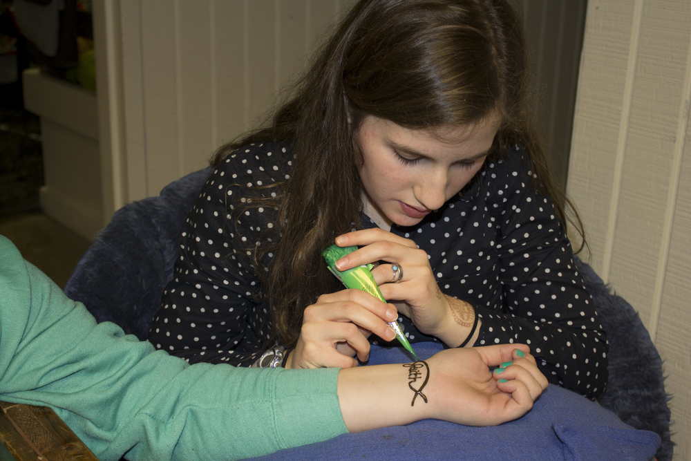 Sophomore Meg Darby enjoys the laid back atmosphere of being able to chat while doing some henna for her roommate and some guy friends that stopped by her dorm.
