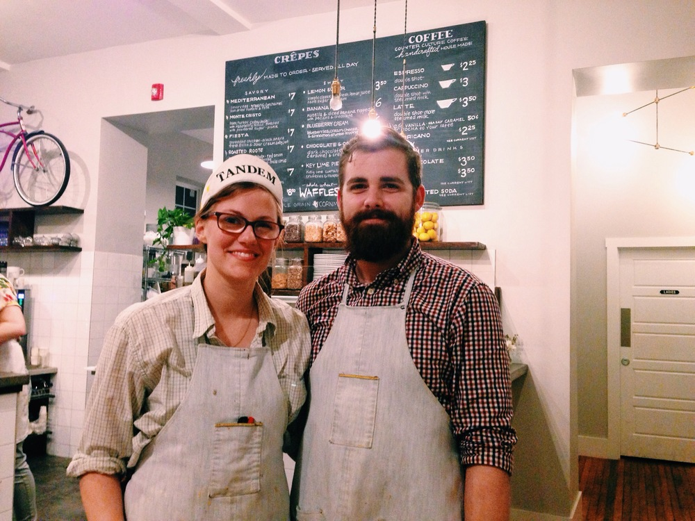 Brad and Kristen Hartman pose for a photo in front of Tandem's menu. See the light bulb above his head? His brilliant idea was Tandem.