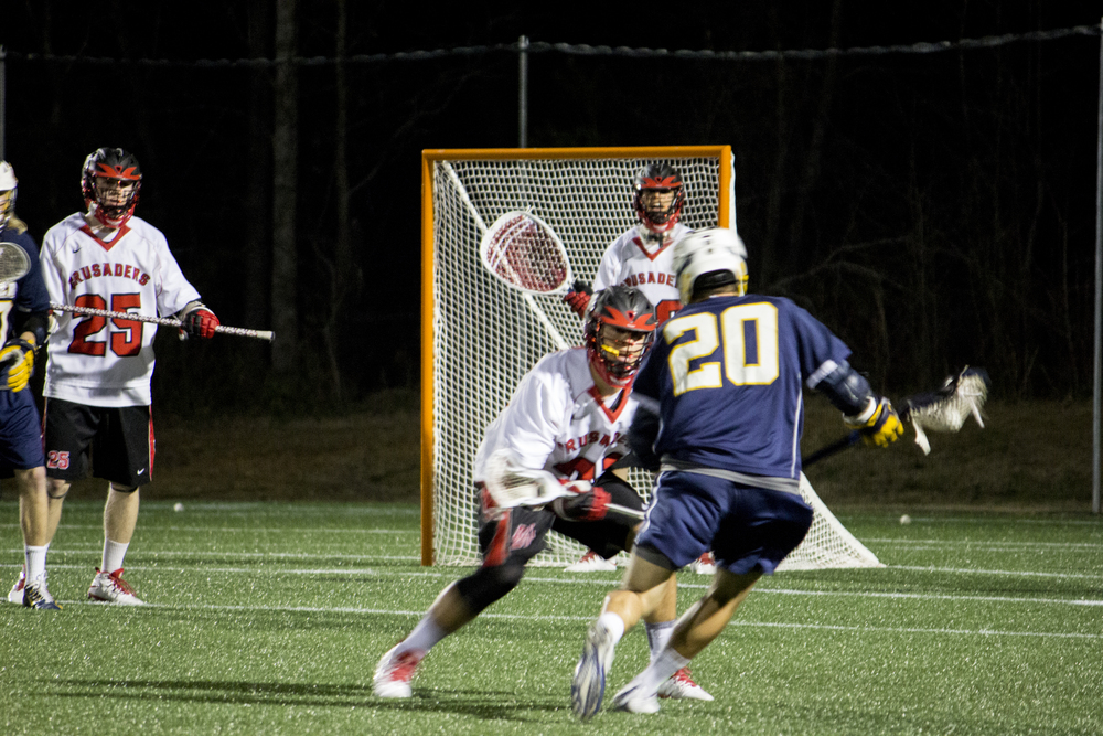 Freshman Allen McBride keeps himself between the goalie and #20 to prevent the shot from being taken.