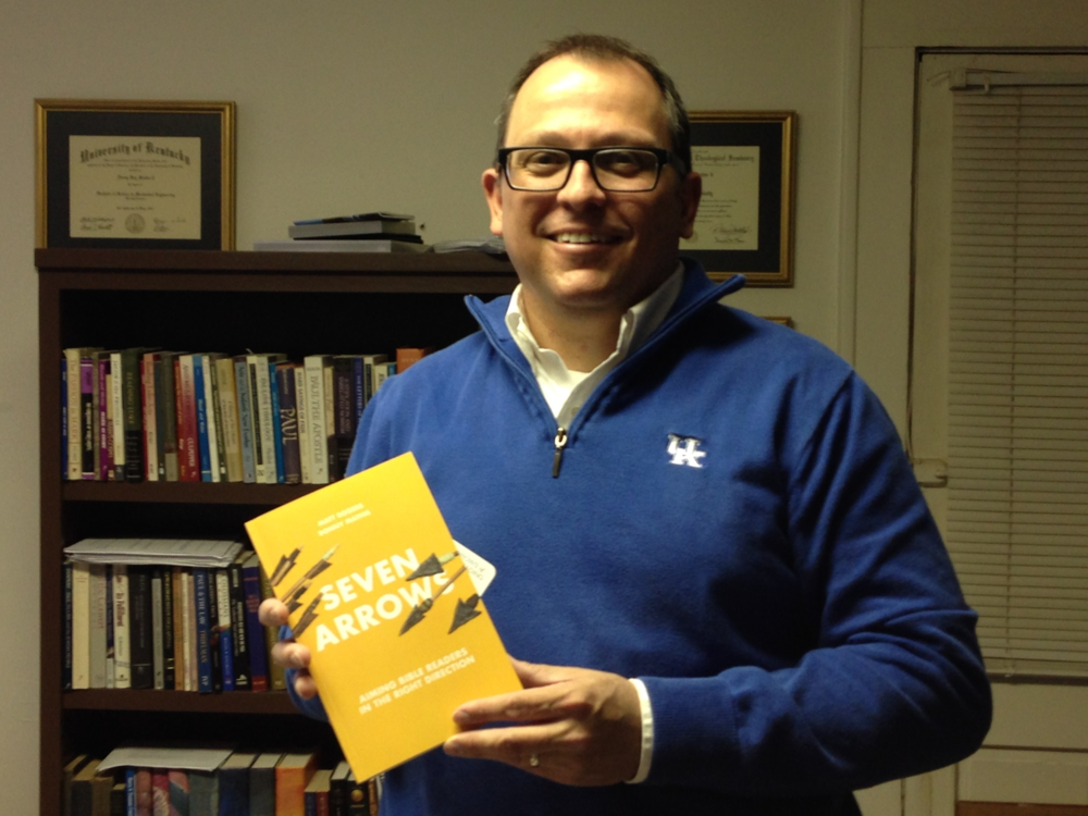 "Donny Mathis, a professor of Christian Studies at NGU, proudly displays his new book ""Seven Arrows: Aiming Bible Readers in the Right Direction"" ,  a comprehensive guide to studying the Scriptures."